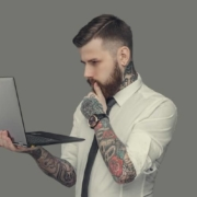 Bearded man in white shirt holding laptop. Isolated on grey background.