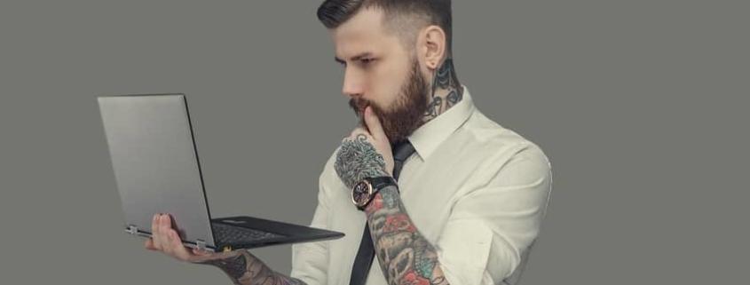 Bearded man in white shirt holding laptop. Isolated on grey background.